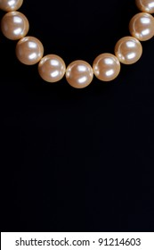 Beige necklace on a black background close up