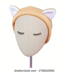 Beige or nude color handmade headband with cat ears as decoration made out of fur fabric texture placed on mannequin head with beautiful eyelashes. This hair band is great as skincare headband.