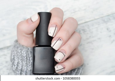 beige Nude manicure with geometric print with dots and lines with nail polish bottle in hand