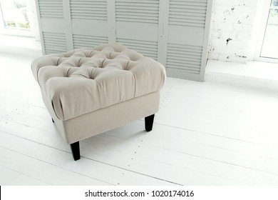 Beige ottoman in a bright room near the window. Element of a decor of a stylish interior. Modern living room interior with furniture. Concept Interior Things Copy Space. Selective focus