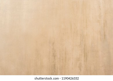 Beige painted wall of an old house with worn plaster and concrete manifestation. Background.