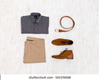 Beige pants, grey shirt, brown suede shoes and leather belt. Overhead view of men's casual outfit on white wooden background. Flat lay, top view.