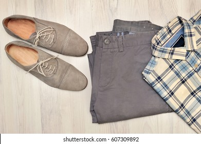 Beige pants, plaid shirt and brown suede shoes. Overhead view of men's casual outfits on white wooden background.