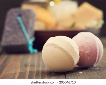 Beige and pink bath bombs closeup with spa products on background. Pastel toned
