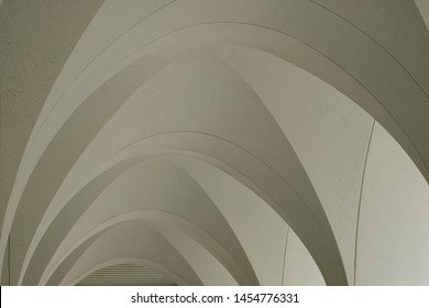 Beige plaster underside of white concrete arches in a mosque colonnade.