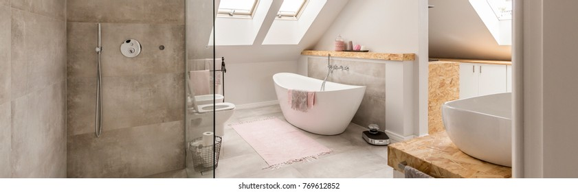 Beige rug on the floor in front of white bathtub in grey bathroom in the attic with shower set