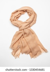 Beige scarf on white background. Top view.
