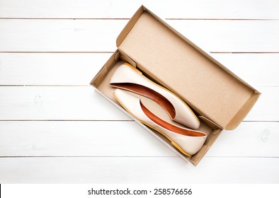 beige shoes flats in a box on a white background