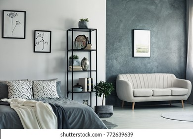 Beige sofa against concrete wall with painting in bedroom with drawings on white wall