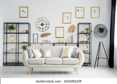 Beige sofa with gold cushions in bright living room interior with industrial lamp and posters