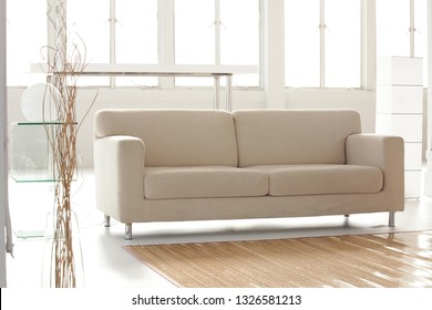 a beige sofa put on center of setup of living room in white room studio for shooting a movie