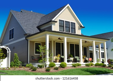 Beige Suburban American Cape Cod Home with Large Front Porch
