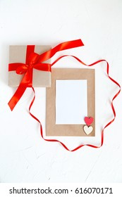 a Beige Vintage Envelope and a Blank Sheet of a White Paper , a Gift Box with red Ribbon on White Stone Background Holiday Concept Top View