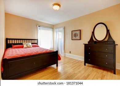 Beige walls bedroom with hardwood floor and bright windows. Furnished with dark brown bed and dresser
