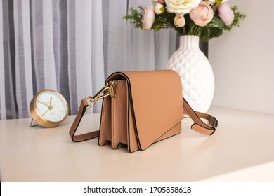 Beige women's leather bag with on a white table with a vase, flowers and a clock in the background