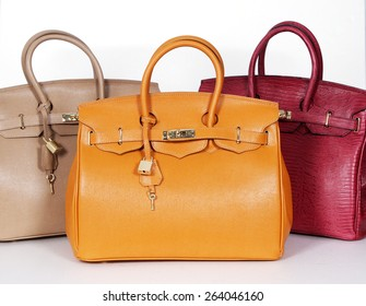 Beige,purple and yellow handbags from genuine leather isolated on white background