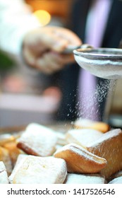 Beignet , The chef is sprinkling sugar powder on a dessert made from deep-fried choux pastry called Beignet.