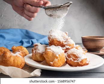 Beignet sprinkled with icing sugar on a wooden table with coffee and milk