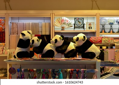 Beijing Airport, China, 2020. Cute panda stuffed toys decorated in a souvenir shop. Chinese fans and stoles are seen in the background in the store