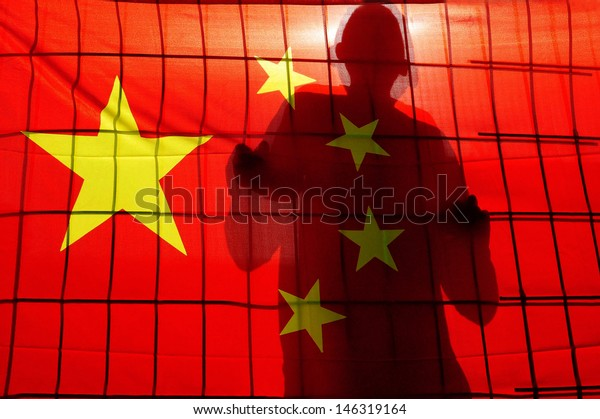 BEIJING - APR 24 2009:Shadow of Chinese man climbing a fence behind China flag.There are about 1.5 million people in prison in China. China does not allow outsiders to inspect it's penal system.