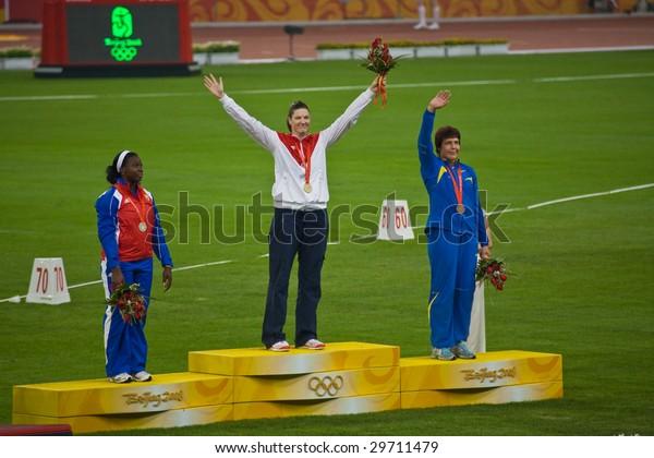 BEIJING - AUG 16: Stephanie Trafton Brown, USA, receives the gold medal for women's Discus throw.  Yarelys Barrios, Cuba, silver. Olena Antonova, Ukraine, bronze. August 16, 2008 Beijing, China