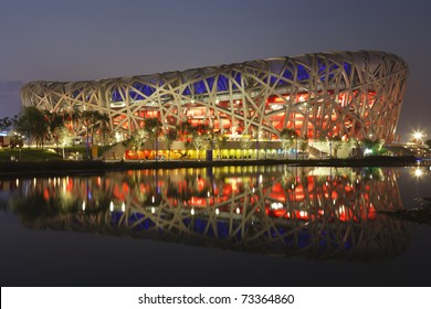 """BEIJING - AUGUST 5:  The National Stadium referred to as the """"Bird's Nest"""" is lit at dusk for an opening ceremony dress rehearsal prior to the 2008 Olympic Games August 5, 2008 in Beijing, China."""