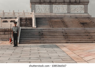 Beijing / China - 08/22/2017: A Chinese guard at the foot of the Monument to the heroes of the people in Tienanmen Square in Beijing
