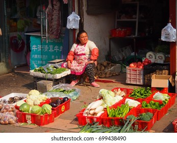 Beijing, China - 10 October, 2016: A woman sits outside her vegetable stall in a Beijing hutong