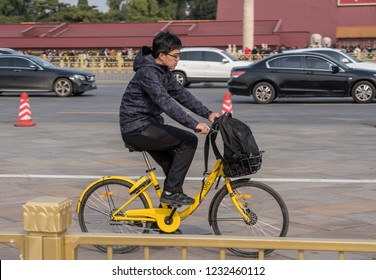 BEIJING, CHINA - 19 OCTOBER 2018: Cyclist on Ofo bike by Forbidden City in Tiananmen Square in Beijing