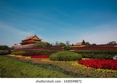 Beijing, China - 2019-04-17: The colorful flowers at the entrance of the Tiananmen Gate or the Gate of Heavenly Peace with  entrance into Forbidden City showing a portrait of Mao Zedong in  China