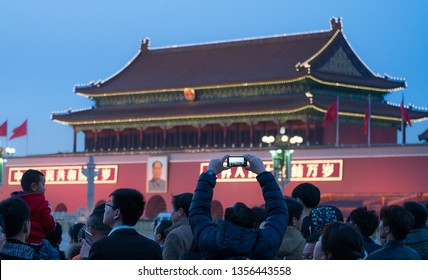Beijing, China - 5 March 2016 : Unidentified people waiting to see and take photos flag-raising and the Chinese soldiers march in Beijing's Tiananmen Square.