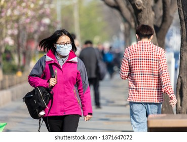 BEIJING, CHINA - APRIL 03, 2019: An unidentified woman is seen wearing a face mask at city downtown.