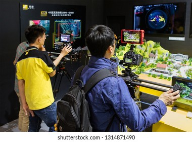 BEIJING, CHINA - APRIL 24, 2016: Visitors try some products at the Nikon booth during the 19th China International Photography & Electrical Imaging Machinery and Technology Fair.