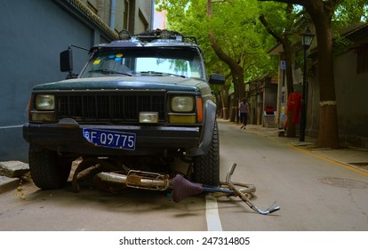 BEIJING, CHINA, AUGUST 20, 2013: bicycle run over by a jeep inside of the hutong area of beijing