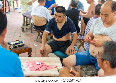 Beijing / China - August 5th 2015: Men playing cards outside, trying to cool off in summer heat by rolling up their T-shirts, streets of Beijing, China