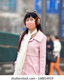 BEIJING, CHINA - DEC 8, 213: A woman is seen with face mask; a high-ranking environmental official has estimated cleaning up China's air pollution will cost 1.75 trillion yuan between 2013 and 2017