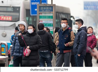 BEIJING, CHINA - DECEMBER 11, 2016: Unidentified people using facemask are seen at a bus stop in city downtown. Today, China's meteorological authorities issued a yellow alert for smog.
