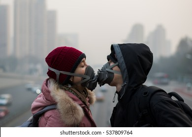 BEIJING, CHINA - DECEMBER 17, 2016: An unidentified couple try to kiss during air pollution in Beijing. Air pollution is a serious problem in Beijing.