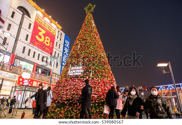 BEIJING, CHINA - DECEMBER 18, 2016:  Unidentified people hang their Christmas wishes, written on strips of colored paper, on the branches of a Christmas tree at Xidan Shopping Center.