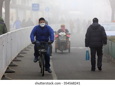 BEIJING, CHINA - DECEMBER 23, 2015: An unidentified man ride a bicycle in smog, in a foggy and hazy day. Beijing issued a red alert for air pollution on Friday, its second red alert this month.