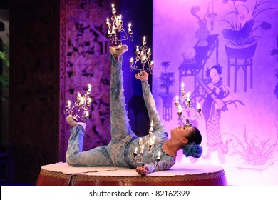 BEIJING, CHINA - DECEMBER 3: Chinese girl performs candle acrobatics onstage at Dazhaimen hall on 3 December, 2009 in Beijing, China