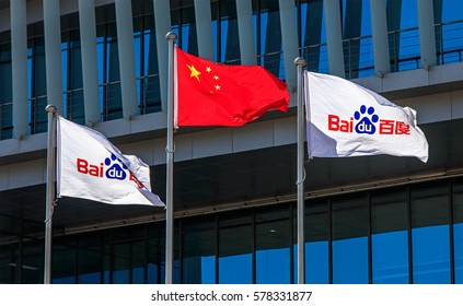 BEIJING, CHINA- FEBRUARY 11, 2017: National flag of China is flanked by Baidu company flags at the Baidu Inc. headquarter. Baidu Inc. is a Chinese web services company, founded in 2000.