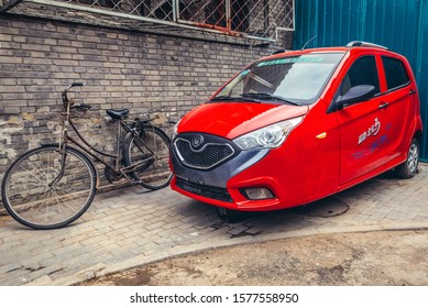 Beijing, China - February 6, 2019: Red three wheeled car in hutong area of Dongcheng district of Beijing capital city