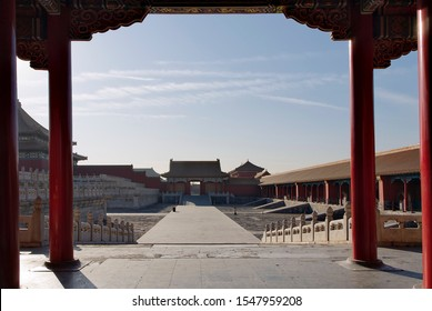 Beijing, China - January 10, 2018: view through an ancient red gate with gold decorations to the square with historical buildings. The Imperial Palace in BeijingImperial Palace, Forbidden City