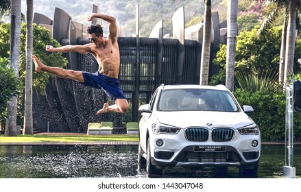 beijing, china- january 19,2018: A bare-chested Asian muscle man flies and kicks next to a BMW X1 SUV