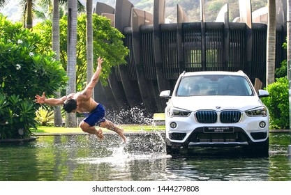 beijing, china- january 19,2018: A bare-chested Asian muscle man is doing forward salto next to a BMW X1 SUV