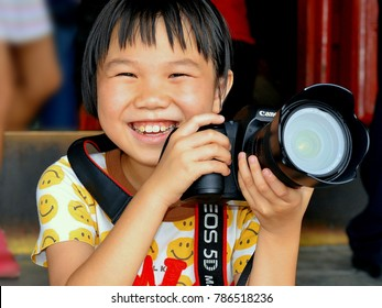 BEIJING, CHINA - JULY 10, 2012: Smiling little Chinese girl photographer holds her heavy Canon DSLR camera with both hands at Beijing's Wanchun Pavilion, on July 10, 2012.
