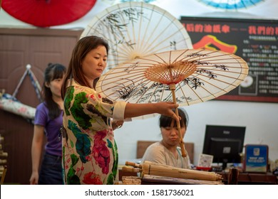 Beijing / China - July 17, 2016: Chinese woman looking at the decorated Chinese oil-paper umbrellas in a traditional handicrafts shop in Beijing