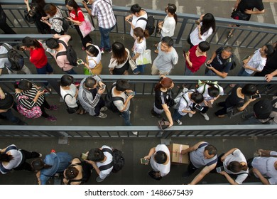 Beijing, China - July 17, 2019: Commuters preoccupied with their smartphones at the Dawang Bridge bus station during evening rush hour.
