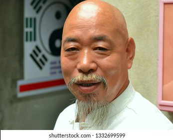BEIJING, CHINA - JULY 19, 2012: Elderly, baldheaded Chinese doctor, astrologer and fortune teller with a moustache and grey chin beard (Chinese goatee) poses for the camera, on July 19, 2012.
